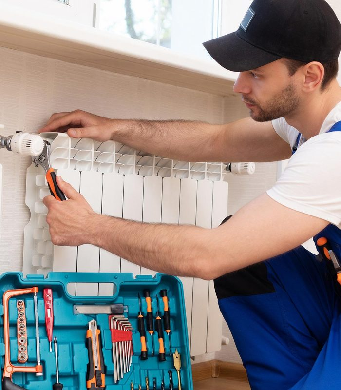 Professional young repairman in special uniform with tools is installing radiators and thermostat in domestic room